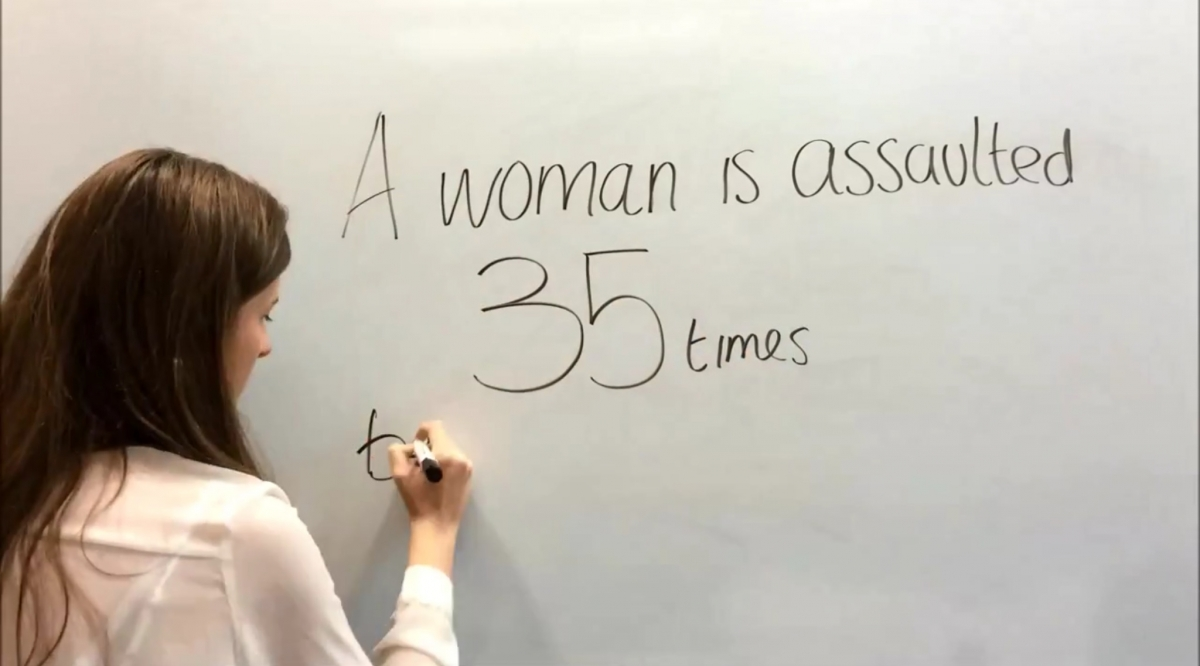 """""""A woman is assaulted 35 times..."""" a girl writes on a board"""